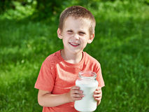 Boy with jug of milk in sunny garden Royalty Free Stock Image