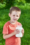 Boy with jug of milk in sunny garden Royalty Free Stock Photo