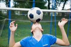 Boy juggling a soccer ball Stock Photography