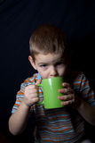 BOY WITH JUICE CUP. The boy drinks from morning warm milk for health Royalty Free Stock Photo