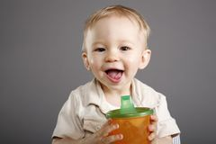 Boy with juice cup. Cute little blond boy with a cup of juice Stock Photos