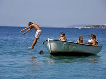 Boy jump from the boat into the sea. Boy and girls in summer holiday on Adriatic sea royalty free stock image
