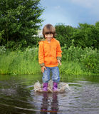 Boy jump in puddle Stock Photos