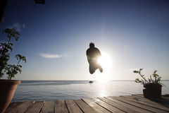 Boy jump into the sea from the platform in the evening Royalty Free Stock Photography