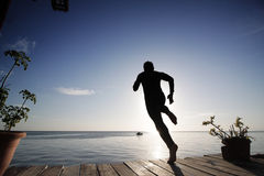 Boy jump into the sea from the platform in the evening Stock Photography