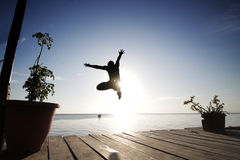 Boy jump into the sea from the platform in the evening Stock Photos