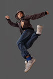 Boy in a jump simulates a dance element. Boy in a jump simulates a dance elemant on a gray background Royalty Free Stock Photography