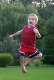Boy Jumping. Making funny faces Stock Image