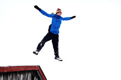 Boy jumping. From a roof into snow Stock Photo