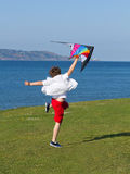 A boy jumping. A happy boy jumping with a colorful kite Royalty Free Stock Image