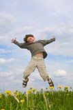 Boy jumping. On green meadow royalty free stock photography