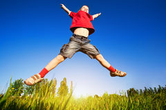Boy jumping against the blue sky. Background Royalty Free Stock Image