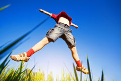 Boy jumping against the blue sky. Fanny boy jumping against the blue sky background Royalty Free Stock Photography