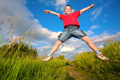 Boy jumping against the blue sky. Boy jumping on the meadow against the blue sky background Stock Images