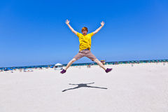 Boy jumping in the air at the beach Royalty Free Stock Photography