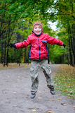 Boy jumping in autumn park Royalty Free Stock Photo