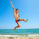 Boy jumping on the beach Royalty Free Stock Photos