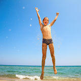 Boy jumping on the beach Royalty Free Stock Images
