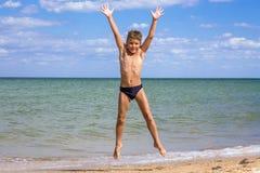 Boy jumping on the beach. Adorable boy jumping on the beach against blue sky Stock Photos