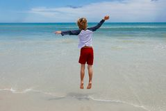 Boy jumping on the beach in front of ocean waves. Young Caucasian blonde boy jumping on beach sand at the edge of the waves in front of the colorful ocean an royalty free stock images