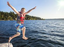 Boy jumping into a beautiful mountain lake. Having fun on a summer vacation. Having fun on a summer vacation. Excited expression on his face and arms raised stock photography