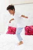 Boy Jumping On Bed Wearing Pajamas Stock Photos