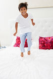 Boy Jumping On Bed Wearing Pajamas Royalty Free Stock Photography