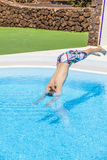 Boy  jumping in the blue pool Royalty Free Stock Photo