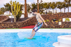 Boy  jumping in the blue pool Stock Photography