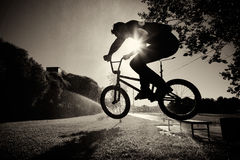 Boy jumping on bmx inside splashes. Backlight  sun summer early morning sunny weather clear sky balck and white photo Stock Photo