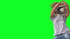 Boy jumping and catching rugby ball on green screen Stock Images