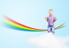 Boy jumping on clouds and a rainbow Royalty Free Stock Photography