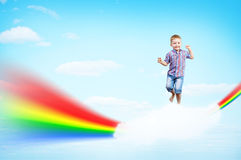 Boy jumping on clouds and a rainbow Stock Image
