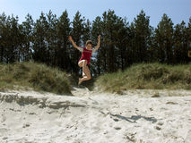 Boy jumping of the dune. A boy jumping from dune by the sea Royalty Free Stock Photos