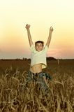 Boy jumping in field Stock Photo