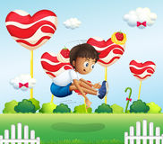 A boy jumping in the field with giant lollipops Stock Images