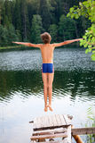 Boy jumping into forest lake Stock Photography