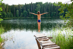Boy jumping into forest lake Royalty Free Stock Photos