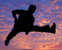 Boy jumping high in the air. Against the sunset Royalty Free Stock Photos