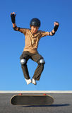 Boy Jumping High from Skateboard. Boy with protective gear jumping high from a skateboard with blue background Royalty Free Stock Photos