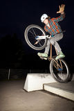 Boy jumping with his bike over a ramp. By night Stock Photos