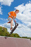 Boy jumping with his scooter Stock Photos