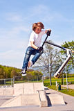 Boy jumping with his scooter Stock Images