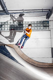 Boy jumping with his scooter in a skate hall Stock Images