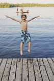 Boy jumping into lake stock photo