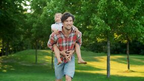 Boy jumping on man back in field. Portrait of happy father carrying son on back