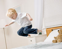 Boy jumping in mid-air on bed in bedroom Stock Images