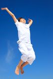 Boy jumping in midair. Barefoot young boy in white summer clothes jumping midair with arms outstretched arms, blue sky background royalty free stock photo