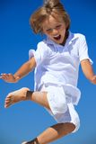 Boy jumping midair. Happy barefoot young boy in shorts jumping midair, blue sky background stock photography