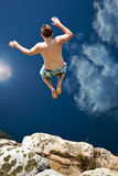 Boy Jumping Off Cliff Into Blue Water Stock Photos